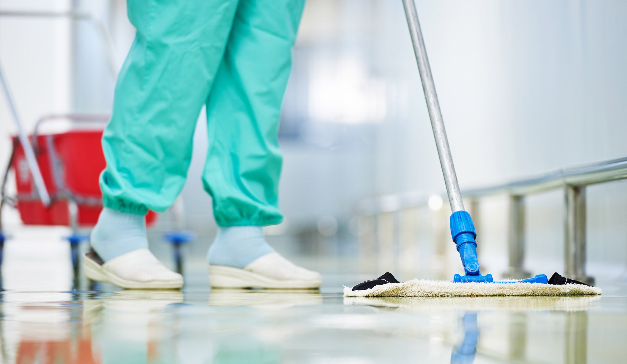 nurse cleaning a floor with a mop